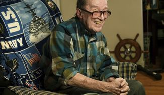FILE - In this November 2014 file photo, Lawrence J. Reilly Sr., a U.S. Navy veteran of World War ll and the Vietnam War, sits in the living room of his home in Syracuse, N.Y. Reilly, a U.S. Navy veteran who survived the 1969 ship collision that claimed the life of his son and later fought unsuccessfully to have the victims' names inscribed on the Vietnam Veterans Memorial has died. Retired Master Chief Lawrence Reilly Sr.'s daughter says he died Wednesday, May 23, 2018, at a Syracuse hospital from complications from pneumonia. He was 93.   (Mike Greenlar /The Syracuse Newspapers via AP, File)
