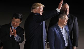 FILE - In this May 10, 2018, file photo President Donald Trump, accompanied by Secretary of State Mike Pompeo, back, waves at the media and others upon arrival of former North Korean detainees Tony Kim, left, Kim Dong Chul and Kim Hak Song, unseen, at Andrews Air Force Base, Md. (AP Photo/Alex Brandon, File)