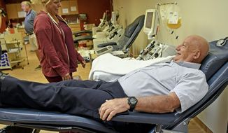 In this Sunday, May 20, 2018 photo, Bill O'Hara, of Washington Township, talks with supervisor Tammy Mayes while making his 500th platelets donation at the Central Blood Bank in Monroeville, Pa. (Jack Fordyce/Pittsburgh Tribune-Review via AP)