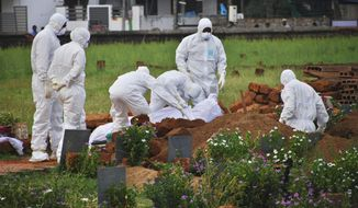 In this Thursday, May 24, 2018, photo, paramedics wear protective suits as a precautionary measure against the Nipah virus as they bury Valachekutti Mosa's body, died of the same virus, in Kozhikode, in the southern Indian state of Kerala. More than 10 people have died of Nipah since an outbreak began earlier this month in Kerala, health officials say. There is no vaccine for the virus, which can cause raging fevers, convulsions and vomiting, and kills up to 75 percent of people who come down with it. (AP Photo/K.Shijith)