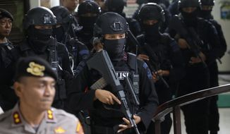 Members of Indonesian police counter terrorism unit Special Detachment 88 escort radical cleric Aman Abdurrahman upon arrival for his trial at a district court in Jakarta, Indonesia, Friday, May 25, 2018. Indonesia's parliament unanimously approved a stronger anti-terrorism law on Friday, lengthening detention periods and involving the military in counter-terrorism policing, spurred into action by recent bombings that involved children as perpetrators. (AP Photo/Tatan Syuflana)
