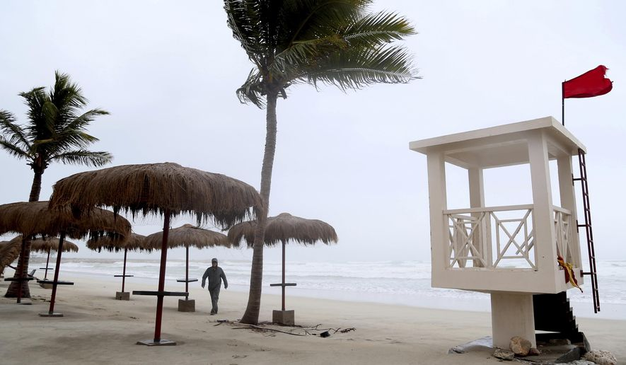 """A man walks down the stormy beach at a hotel in Salalah, Oman, Friday, May 25, 2018. Cyclone Mekunu will be """"extremely severe"""" when it crashes into the Arabian Peninsula this weekend, meteorologists warned Friday, after earlier thrashing the Yemeni island of Socotra. (AP Photo/Kamran Jebreili)"""