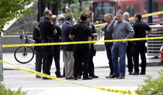 Officials gather at the scene where pedestrians were hit by a motorist in Portland, Ore., Friday, May 25, 2018. Police say three women have been injured in a hit-and-run crash near Portland State University. (AP Photo/Don Ryan)