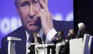 Russian President Vladimir Putin, second right, also seen at a big screen, gestures as Bloomberg Editor-in-Chief John Micklethwai, left, French President Emmanuel Macron, third right, and International Monetary Fund (IMF) Managing Director Christine Lagarde, right, listen to him at the St. Petersburg International Economic Forum in St. Petersburg, Russia, Friday, May 25, 2018. (AP Photo/Dmitri Lovetsky)