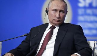 Russian President Vladimir Putin attends the St. Petersburg International Economic Forum in St. Petersburg, Russia, Friday, May 25, 2018. Putin says the global economy has suffered from politically driven sanctions. (AP Photo/Dmitri Lovetsky)