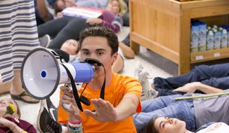 "Marjorie Stoneman Douglas High School student David Hogg speaks as demonstrators lie on the floor at a Publix Supermarket in Coral Springs, Fla., Friday, May 25, 2018. Students from the Florida high school where 17 people were shot and killed earlier this year did a ""die in"" protest at a supermarket chain that backs a gubernatorial candidate allied with the National Rifle Association. Shortly before the ""die-in"" Publix announced that it will suspend political donations. (AP Photo/Wilfredo Lee) ** FILE **"