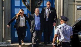Harvey Weinstein, second left, is loaded into an unmarked vehicle while leaving the first precinct of the New York City Police Department after turning himself to authorities following allegations of sexual misconduct, Friday, May 25, 2018, in New York. (AP Photo/Andres Kudacki)
