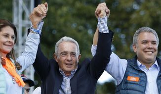 Colombia's former President Alvaro Uribe stands between Ivan Duque, presidential candidate for Democratic Center party, right, and his running mate Martha Lucia Ramirez during a campaign rally in Bogota, Colombia, Sunday, May 20, 2018. Colombians will go to the polls on May 27 for a first round presidential election. (AP Photo/Fernando Vergara)