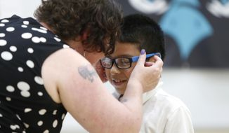In this Wednesday, May 16, 2018  photo, Brenda Loop helps Juan Alvarez-Ramirez put on his new glasses at the Vision to Learn event at Irving Elementary School in Waterloo, Iowa. A mobile clinic provides free screenings, eye exams and glasses to needy students in low-income schools across central and eastern Iowa. Vision to Learn has served students at Waterloo Community Schools, Highland, Lincoln and Lowell elementary schools as well as Dr. Walter Cunningham School for Excellence. (Matthew Putney/The Courier via AP)