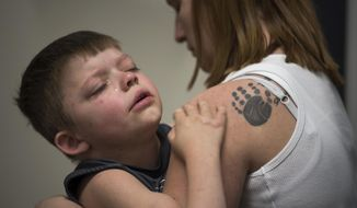 In this April, 24, 2018, photo, Tabitha Fich comforts Austin Justin, 5, as he struggles to practice with his new RGO braces at Shriners Hospitals for Children in Portland, Ore. Tabitha has Austin's hand and foot print from when he was a newborn tattooed on her shoulder. (Alisha Jucevic/The Columbian via AP)