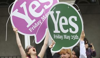 "People from the ""Yes"" campaign react as the results of the votes begin to come in, after the Irish referendum on the 8th Amendment of the Irish Constitution at Dublin Castle, in Dublin, Ireland, Saturday May 26, 2018. The first official results for Ireland's landmark abortion referendum have begun to come in, indicating a landslide win for abortion rights campaigners is likely in diverse constituencies across the country. (AP Photo/Peter Morrison)"