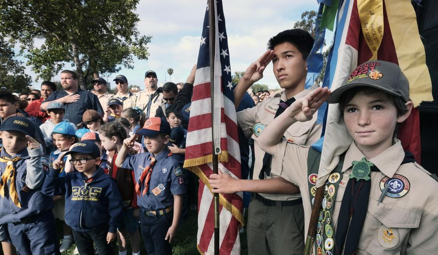 Boy Scouts and Cub Scouts salute the flag during ceremonies at the Los Angeles National Cemetery in Los Angeles on Saturday, May 26, 2018. More than 6,000 Scouts, with the support of local community members, placed 88,000 American flags on graves throughout the cemetery to honor fallen service members in anticipation of Memorial Day. (AP Photo/Richard Vogel) ** FILE **
