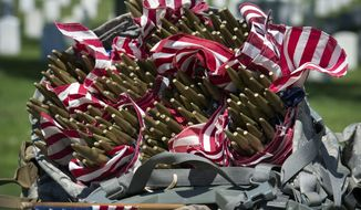 Flags fill the backpack of a members of the Army 3d U.S. Infantry Regiment, The Old Guard, as they place flags at headstone, in honor the nation's fallen military heroes during its annual Flags In ceremony at Arlington National Cemetery,  Thursday, May 24, 2018, in Arlington, Va. (AP Photo/Cliff Owen)