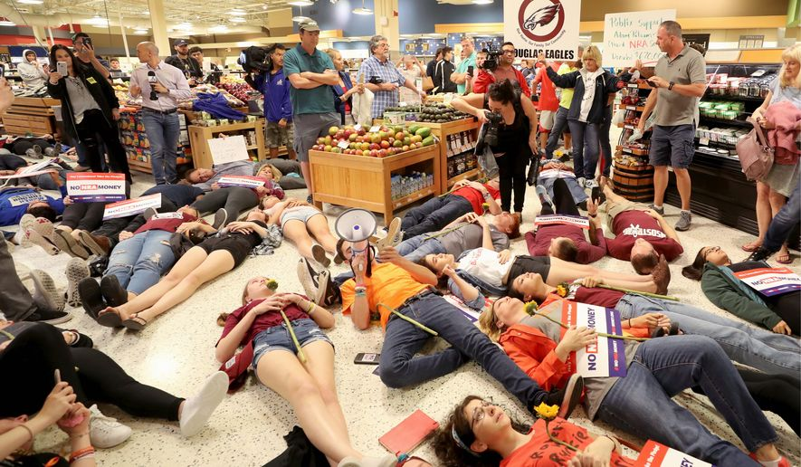 """Demonstrators lie on the floor at a Publix Supermarket in Coral Springs, Florida, on Friday. Students from the Florida high school where 17 people were killed did a """"die in"""" protest at the supermarket chain. (Associated Press)"""