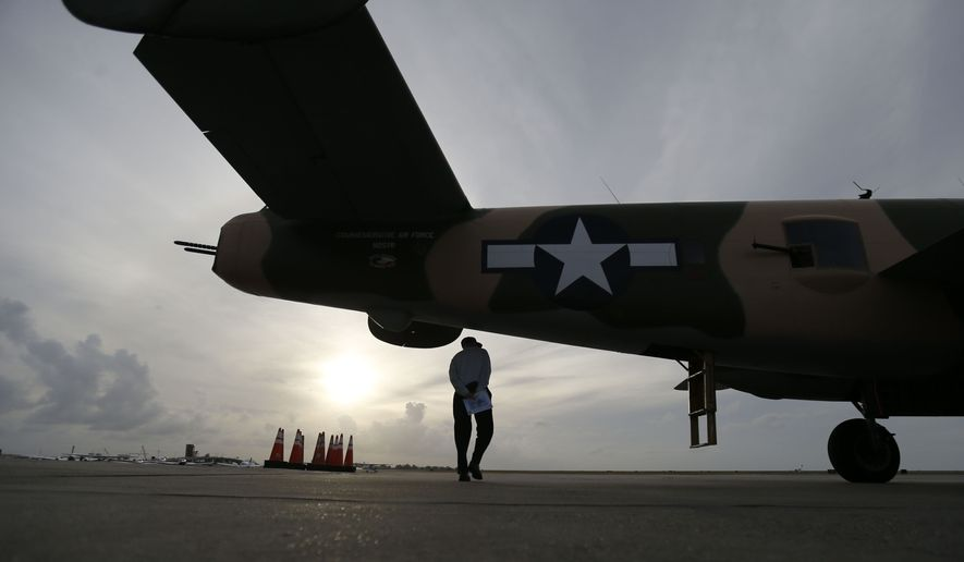 """World War II veteran Mike Fedirko, 91, walks underneath the B-25 Mitchell bomber """"Yellow Rose"""" after he flew aboard the plane at New Orleans Lakefront Airport in New Orleans, Thursday, Oct. 22, 2015. Fedirko flew missions in a B-25 during the war. The planes, part of the Commemorative Air Force, are in town for the WWII AirPower Expo 2015, hosted by the National World War II Museum, which runs through the weekend. (AP Photo/Gerald Herbert)"""