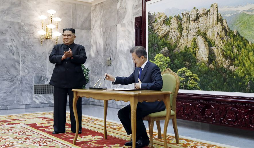 In this May 26, 2018, photo provided on May 27, 2018, by South Korea Presidential Blue House, South Korean President Moon Jae-in writes on a visitor's book as North Korean leader Kim Jong-un, left, stands at the northern side of Panmunjom in North Korea. Kim and Moon met Saturday, May 26, for the second time in a month, exchanging a huge bear hug and broad smiles in a surprise summit at a border village to discuss Kim's potential meeting with U.S. President Donald Trump and ways to follow through on the peace initiatives of the rivals' earlier summit. (South Korea Presidential Blue House via AP)