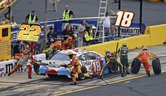 Crew members perform a pit stop on driver Kyle Busch's car during the NASCAR Cup Series auto race at Charlotte Motor Speedway in Charlotte, N.C., Sunday, May 27, 2018. (AP Photo/Mike McCarn)