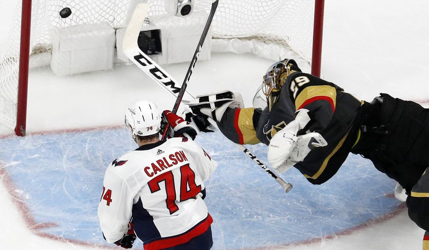 Washington Capitals defenseman John Carlson, left, scores on Vegas Golden Knights goaltender Marc-Andre Fleury during the second period in Game 1 of the NHL hockey Stanley Cup Finals Monday, May 28, 2018, in Las Vegas. (AP Photo/John Locher)