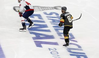 Washington Capitals right wing Tom Wilson, left, and Vegas Golden Knights center Jonathan Marchessault skate through the Stanley Cup Finals logo during the second period in Game 1 of the NHL hockey Stanley Cup Finals Monday, May 28, 2018, in Las Vegas. (AP Photo/Ross D. Franklin)