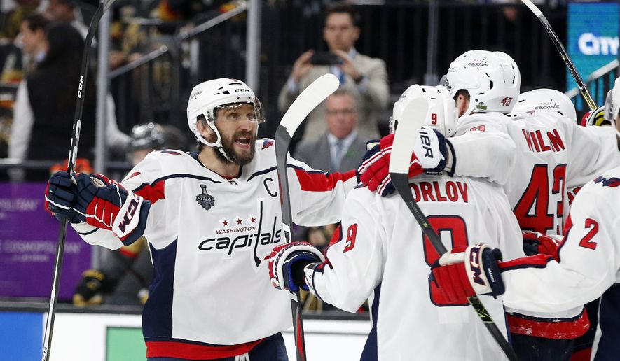 Washington Capitals left wing Alex Ovechkin, left, of Russia, celebrates a goal by right wing Tom Wilson, right, along with defenseman Dmitry Orlov, of Russia, during the third period in Game 1 of the NHL hockey Stanley Cup Finals Monday, May 28, 2018, in Las Vegas. (AP Photo/John Locher)