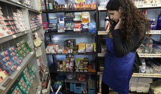In this May 17, 2018 photo, Miriam Zouzounis looks through a selection of tobacco products while interviewed at Ted's Market, her family's store, in San Francisco. R.J. Reynolds Tobacco Co. is pumping millions of dollars into a campaign to persuade San Francisco voters to reject a ban on selling flavored tobacco products, including menthol cigarettes and vaping liquids with flavors like cotton candy, mango and cool cucumber. Zouzounis, a board member of the Arab American Grocers Association, which represents 400 small-business owners in the San Francisco Bay Area, said the ban would remove an anchor product that attracts customers, many of which are immigrant-owned.  (AP Photo/Jeff Chiu)