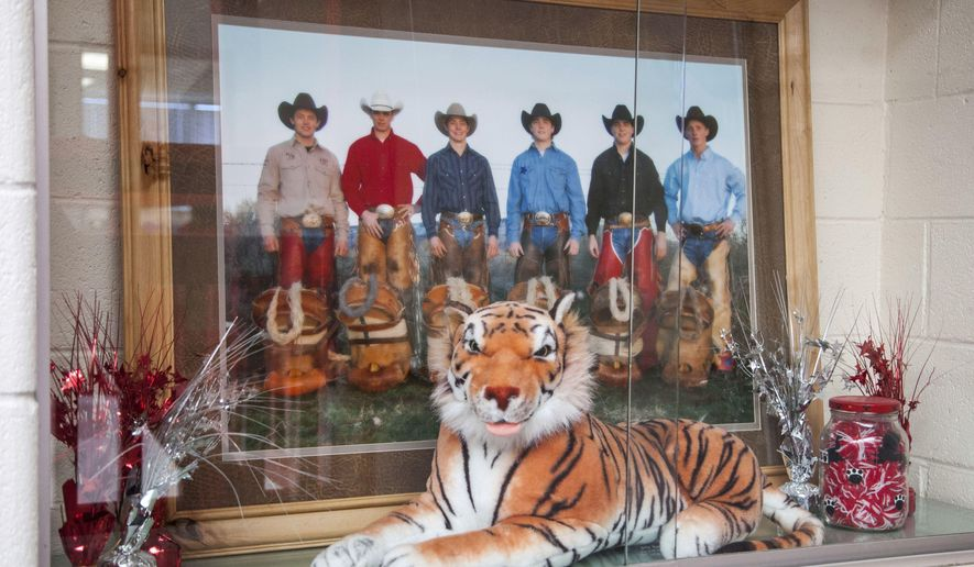 """In this Dec. 8, 2016, photo, a photo of the Wright family sits inside a trophy case at Milford High School. A southern Utah family that has produced several generations of rodeo champions is chronicled in a new book called """"The Last Cowboys."""" (The Spectrum via AP)"""
