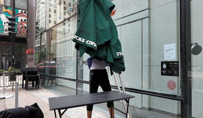 A Starbucks employee takes outside seating umbrellas inside a store in Chicago's famed Loop Tuesday, May 29, 2018, in Chicago. Starbucks is closing more than 8,000 U.S. stores for a few hours Tuesday to conduct anti-bias training in the company's latest effort to deal with the fallout over the arrest of two black men at one of its shops in Philadelphia. (AP Photo/Charles Rex Arbogast)