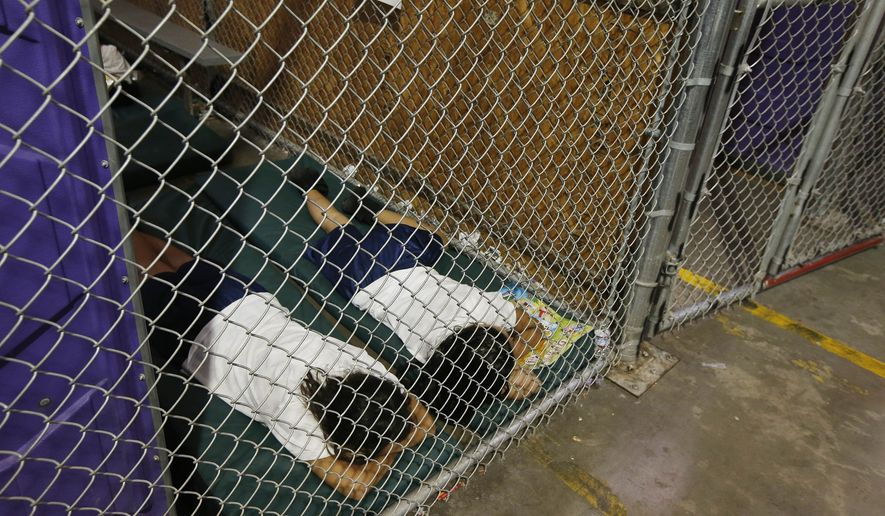Two female detainees sleep in a holding cell, as the children are separated by age group and gender, as hundreds of mostly Central American immigrant children are being processed and held at the U.S. Customs and Border Protection Nogales Placement Center in Nogales, Ariz., on June 18, 2014. (Associated Press) **FILE**