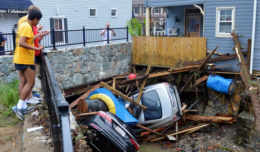 Residents gather by a bridge to look at cars left crumpled in one of the tributaries of the Patapsco River that burst its banks as it channeled through historic Main Street in Ellicott City, Md., Monday, May 28, 2018. Sunday's destructive flooding left the former mill town heartbroken as it had bounded back from another destructive storm less than two years ago. (AP Photo/David McFadden) ** FILE **