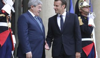 French president Emmanuel Macron, right, welcomes Algerian Prime Minister Ahmed Ouyahia in Paris,Tuesday May 29, 2018. Libya's rival leaders are meeting in Paris to agree on a political roadmap including elections, in an effort to bring order to Libya's chaos, which is feeding Islamic militants, traffics of all kind and instability in the region. (Ludovic Marin, Pool via AP)