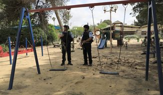 Israeli police officers guard a playground in a kibbutz near the Israel and Gaza border, Tuesday, May 29, 2018. Gaza militants fired more than 25 mortar shells toward communities in southern Israel Tuesday, the Israeli military said, in what appeared to be the largest single barrage fired since the 2014 Israel-Hamas war. (AP Photo/Tsafrir Abayov)
