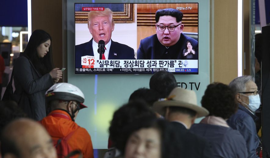 """People watch a TV screen showing images of U.S. President Donald Trump, left, and North Korean leader Kim Jong Un during a news program at the Seoul Railway Station in Seoul, South Korea, Tuesday, May 29, 2018. A team of American diplomats involved in preparatory discussions with North Korea ahead of a potential summit between Trump and Kim left a hotel in Seoul on Tuesday amid speculation that they are resuming the talks. The signs read: """"Working-level talks."""" (AP Photo/Ahn Young-joon)"""