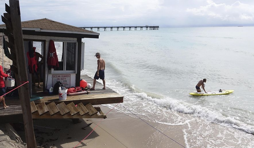 Dania Beach Ocean Rescue lifeguard Michael Vasta paddles out, Tuesday, May 29, 2018, as his colleague Peter Fournier watches from a beach tower in Dania Beach, Fla. (Joe Cavaretta/South Florida Sun-Sentinel via AP)