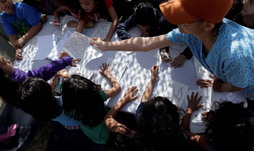 Children detained at a U.S. Customs and Border Protection processing facility color and draw, part of the many activities as well as meals and clothing they are provided at taxpayer expense. (Associated Press)