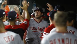 Washington Nationals starting pitcher Max Scherzer, center, high-fives teammates in the dugout after pitching in the eighth inning of a baseball game against the Baltimore Orioles, Wednesday, May 30, 2018, in Baltimore. Scherzer gave up two hits in eight innings as Washington won 2-0. (AP Photo/Patrick Semansky)