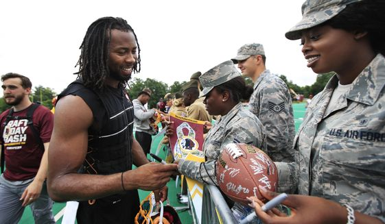 Redskins cornerback Josh Norman, left, signs autographs following the NFL football team's full practice session at the Redskins Park in Ashburn, Va., Wednesday, May 30, 2018. (AP Photo/Manuel Balce Ceneta)