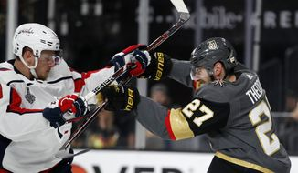 Washington Capitals left wing Jakub Vrana, left, of the Czech Republic, and Vegas Golden Knights defenseman Shea Theodore scuffle during the first period in Game 2 of the NHL hockey Stanley Cup Finals on Wednesday, May 30, 2018, in Las Vegas. (AP Photo/John Locher)