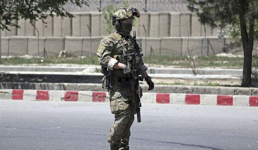 A U.S. soldier arrives at the site of deadly attack on the interior ministry, in Kabul, Afghanistan, Wednesday, May 30, 2018. Afghan officials said a suicide bomber struck outside the ministry, allowing gunmen to pass through an outer gate where they traded fire with security forces, who eventually killed the attackers. (AP Photo/Rahmat Gul)