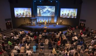 In a Sunday, May 20, 2018 photo, the congregation prays during the musical portion of services at the Ethiopian Evangelical Baptist Church in Garland, Texas. The church was founded around 1983 after a few Dallas-area residents from Ethiopia began to have services at a park. It recently moved into the former Orchard Hills Baptist Church building. (Rex C. Curry/The Dallas Morning News via AP)