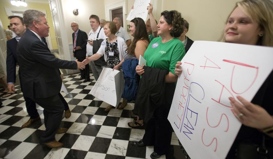 State Sen. Bill Stanley, R-Franklin County, left, shakes the hand of a demonstrator at the Capitol in Richmond, Va., Wednesday, May 30, 2018. The Senate is due to vote on a budget proposal today. (AP Photo/Steve Helber)