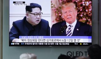 "FILE - In this May 26, 2018, file photo, people watch a TV screen showing file footage of U.S. President Donald Trump, right, and North Korean leader Kim Jong Un during a news program at the Seoul Railway Station in Seoul, South Korea. When Trump and Kim meet in Singapore next month, they will have two very different agendas. Kim would love to keep his nukes. And Trump would love to take them all away, ASAP. The letters read ""if the summit does happen, will likely take place on June 12 in Singapore."" (AP Photo/Lee Jin-man, File)"