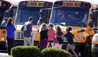 """Students exits their buses as they return to class for the first time at Noblesville West Middle School in Noblesville, Ind., Wednesday, May 30, 2018.  Noblesville Schools' spokeswoman Marnie Cooke says it will operate on the same shortened schedule as the district's final two days of classes Thursday and Friday. Cooke says the school will focus on counseling and """"team building"""" over the final three days of the school year.  (AP Photo/Michael Conroy)"""