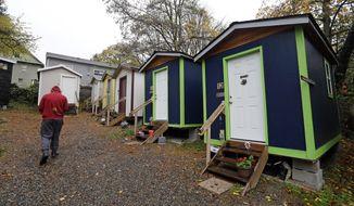 FILE- In this Nov. 9, 2017 file photo, a resident walks past a row of tiny houses at a homeless encampment in Seattle where full size homes stand behind. Seattle Mayor Jenny Durkan wants to move hundreds more homeless people into tiny homes, emergency shelters and other immediate housing in the next 90 days. (AP Photo/Elaine Thompson, file)