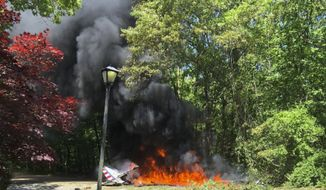 This photo provided by Lauren Peller shows a small airplane that crashed in Melville, N.Y., Wednesday, May 30, 2018. The small vintage airplane that was part of a GEICO stunt team of five other planes crashed in the wooded residential area on Long Island, killing its pilot, Suffolk County police said Wednesday. (Lauren Peller via AP)