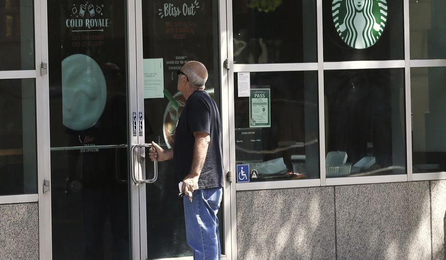 A man finds the doors locked and a sign explaining why the store closed early, Tuesday, May 29, 2018, in Sacramento, Calif. Starbucks closed more than 8,000 stores nationwide Tuesday to conduct anti-bias training, the next of may steps the company is taking to try to restore its tarnished image as a hangout where all are welcome. (AP Photo/Rich Pedroncelli)