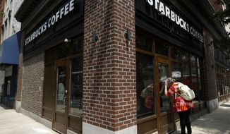 A woman peers into a closed Starbucks Coffee shop, Tuesday, May 29, 2018, in Philadelphia. After the arrests of two black men, Rashon Nelson and Donte Robinson, Starbucks will close more than 8,000 stores nationwide on Tuesday to conduct anti-bias training, the next of many steps the company is taking to try to restore its tarnished image as a hangout where all are welcome. (AP Photo/Matt Slocum)