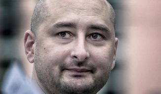 In this photo taken on Friday, Aug. 9, 2013, Arkady Babchenko, 41, who had been scathingly critical of the Kremlin in recent years, looks at an opposition picket in Moscow, Russia. Police in the capital of Ukraine say a Russian journalist has been shot and killed at his Kiev apartment. Ukrainian police said Arkady Babchenko's wife found him bleeding at the apartment on Tuesday, May 29, 2018 and called an ambulance, but Babchenko died on the way to a hospital. (AP Photo/Alexander Baroshin)