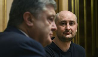 Ukrainian President Petro Poroshenko, left, and Russian journalist Arkady Babchenko speak during their meeting in Kiev, Ukraine, Wednesday, May 30, 2018. Babchenko , who was reported shot dead in the Ukrainian capital on Tuesday showed up at a news conference on Wednesday, saying that the security services faked his death in order to thwart a plot on his life. (Mykola Lazarenko/Presidential Press Service Pool Photo via AP)