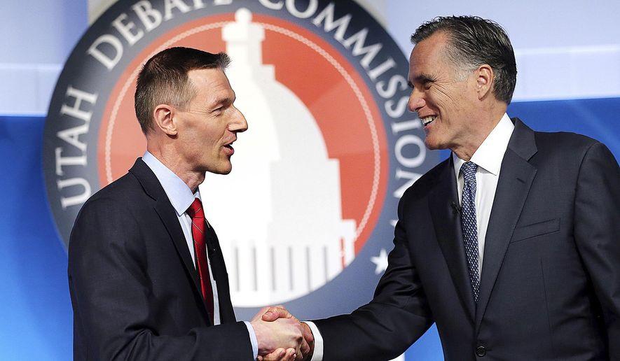 Utah Senate candidates, state Rep. Mike Kennedy, R-Alpine, left, and former Massachusetts Gov. Mitt Romney shake hands at the beginning of a Senate Republican primary debate, Tuesday, May 29, 2018, in Provo, Utah. (Scott G Winterton/The Deseret News via AP, Pool)