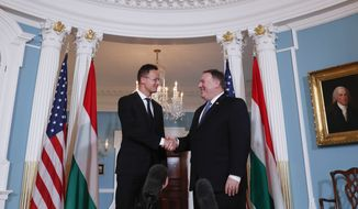 Secretary of State Mike Pompeo, right, shakes hands with Hungarian Minister of Foreign Affairs and Trade Peter Szijjarto, left, during their meeting at the US State Department in Washington, Wednesday, May 30, 2018. (AP Photo/Pablo Martinez Monsivais)